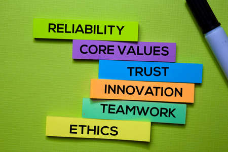 Reliability, Core Values, trust, Innovation, Teamwork, Ethics text on sticky notes isolated on green desk. Mechanism Strategy Concept Stock Photo
