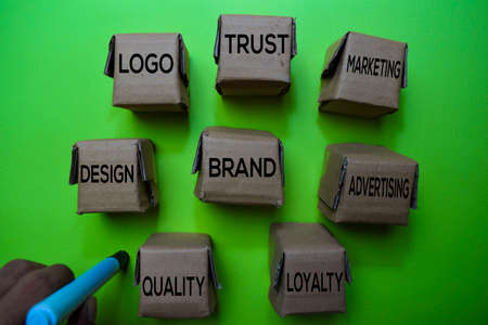 Brand, Design, Logo, Trust, Marketing, Advertising, Loyalty, Quality text on box isolated on green desk. Mechanism Strategy Concept Stock Photo
