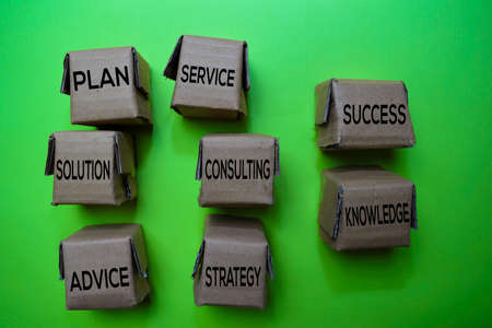 Consulting, Solution, Plan, Service, Success, Knowledge, Strategy, Advice text on box isolated on green desk. Mechanism Strategy Concept Stock Photo