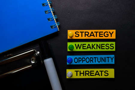 Strategy, Weakness, Opporunity, Threats (SWOT) text on sticky notes isolated on Black desk. Mechanism Strategy Concept