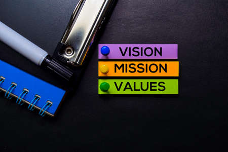 Vision, Mission, Values text on sticky notes isolated on Black desk. Mechanism Strategy Concept