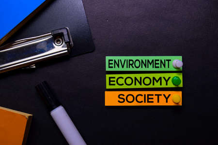 Environment, Economy, Society text on sticky notes isolated on Black desk. Mechanism Strategy Concept