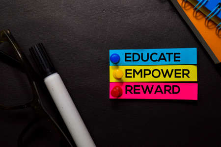 Educate, Empower, Reward text on sticky notes isolated on Black desk. Mechanism Strategy Concept Stock Photo