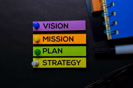 Vision, Mission, Plan, Strategy text on sticky notes isolated on Black desk. Mechanism Strategy Concept