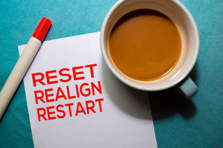 Reset Realign Restart text on the paper isolated on office desk background Stock Photo