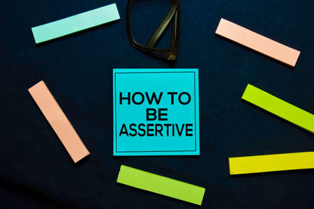 How To Be Assertive text on sticky notes isolated on office desk. Фото со стока