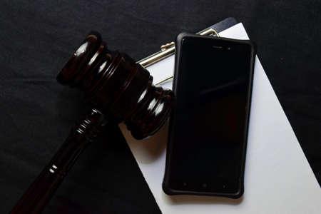 Black Judges gavel and Smartphone on office desk. Law concept