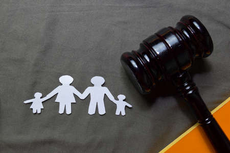 Black Judges gavel and Family Figure made in paper on office desk. Law concept