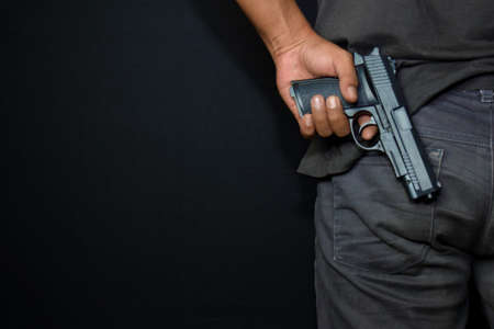 asian man holds a gun. Gun in his hand from the back isolated on black background.