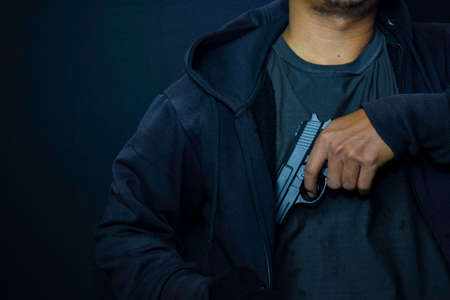 asian man holding a gun. Gun in his hand background of a leather jacket