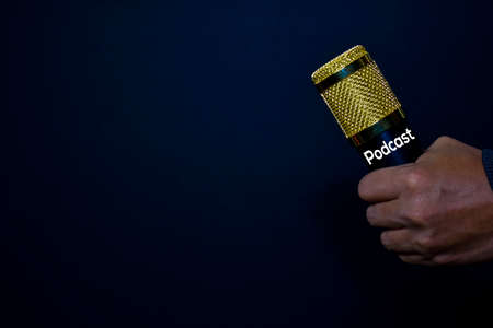 Profesional Microphone on hands isolated black background. Podcast Concept