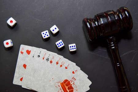 juego de naipes y martillo aislado sobre fondo negro. concepto de casino