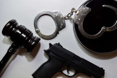 gun, handcuffs and black gavel isolated on white background. Justice and law concept