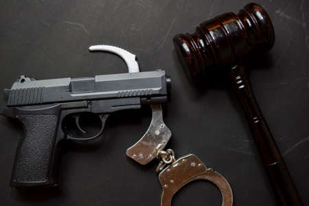 gun, handcuffs and black gavel isolated on black background. Justice and law concept Stock Photo