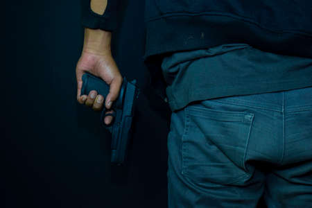 asian man holds a gun. Gun in his hand isolated on black background.