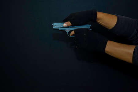 asian man holds a gun. Killed shooting his target isolated on black background.