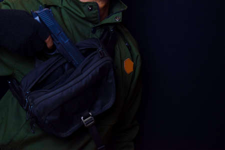 asian man holding a gun. Gun in his hand background of a waist bag