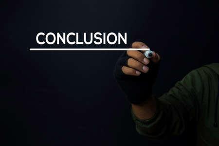 A man write a conclusion with a black background Banco de Imagens - 131626990