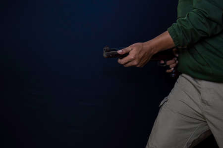 asian man holds a gun. Gun in his hand. Killed shooting his target isolated on black background.