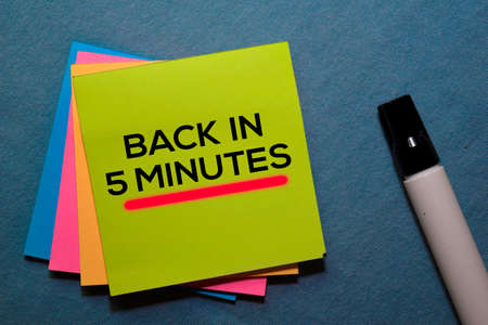 Back in 5 Minutes on sticky notes isolated on Office Desk