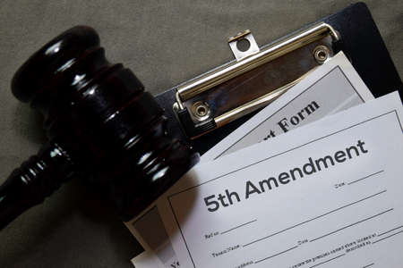 5th Amandment text on Document and gavel isolated on office desk. Law concept Banco de Imagens