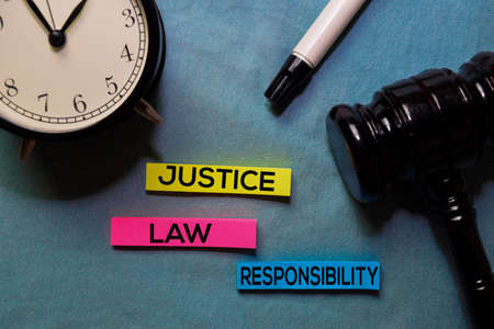 Justice, Law, and Responsibility on sticky notes and gavel isolated on office desk. Law concept