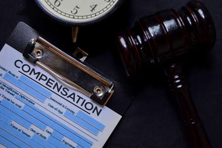Compensation text on Document and gavel isolated on office desk. Law concept Фото со стока