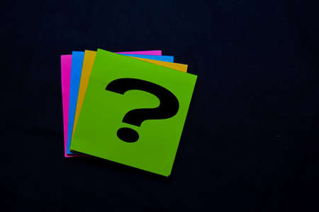 Question mark on sticky notes isolated on black background