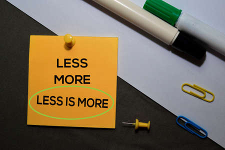 Less is More on sticky notes isolated on black white background Zdjęcie Seryjne