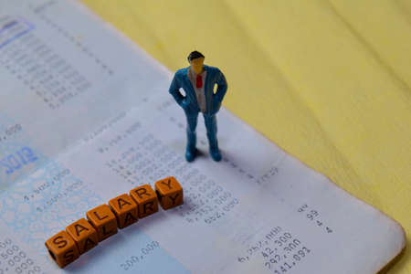 Miniature people standing on bank deposite account with Salary on wooden blocks.