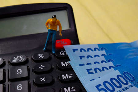 Miniature people standing on calculator and Indonesian Rupiah. Interest rate cut percentage and Finance concept