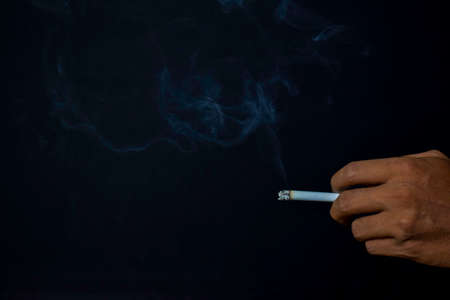 Hand of asian man holding cigarettes with black background. Smoking cigarettes concept Stock Photo