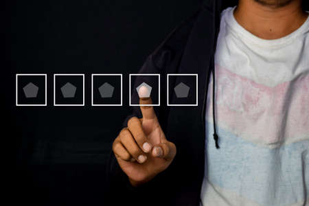 Asian Man pointed and give rating for 4 star icon for customer isolated on black background Stok Fotoğraf