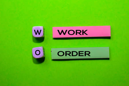 WO - Work Order acronym write on sticky notes isolated on Green background.