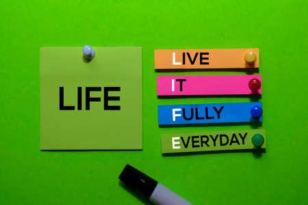 LIFE. Live it Fully Everyday acronym on sticky notes. Office desk background