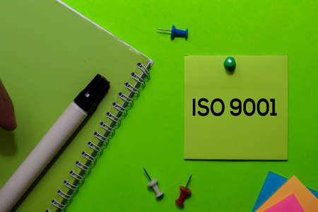 ISO 9001 write on sticky notes. Isolated on green table background