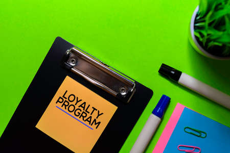Loyalty Program write on sticky notes. Isolated on green table background