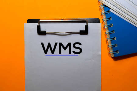 WMS write on paperwork. Isolated on orange table background