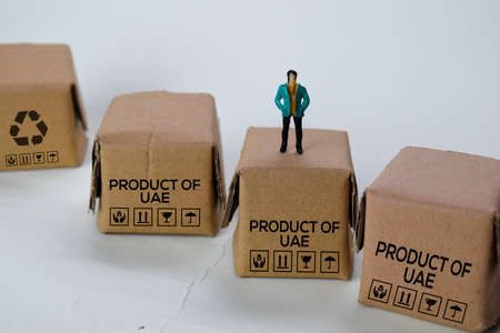 Miniature businessman Standing on Boxes with text Made in Product Of UAE isolated white bakground Stockfoto