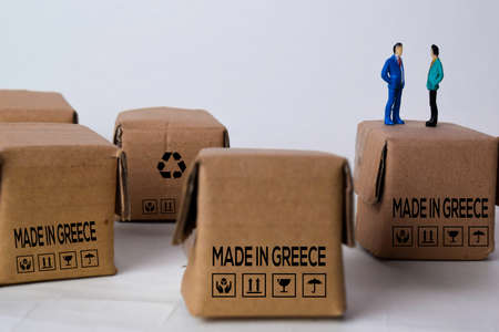 Miniature businessman Talking on Boxes with text Made In Greece isolated white bakground