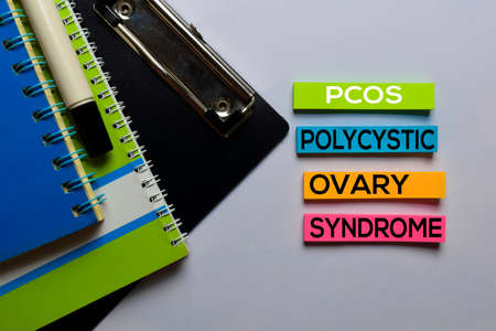 PCOS. Polycystic Ovary Syndrome write on sticky notes. Isolated on white table background Stock Photo