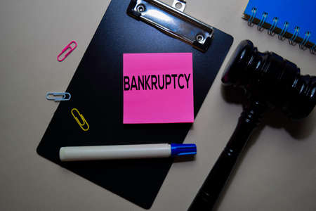 Bankruptcy text on sticky notes and gavel isolated on office desk. Justice law concept