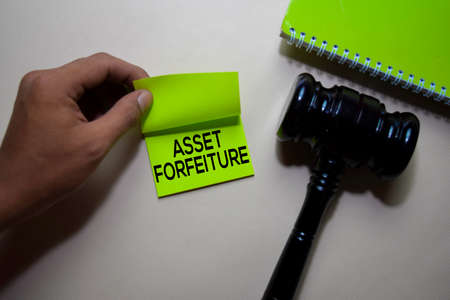 Asset Forfeiture text on sticky notes and gavel isolated on office desk. Justice law concept