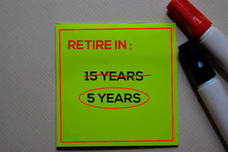 Retire in 15 Years and circle around 5 years text on sticky notes at office desk.