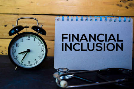 Financial Inclusion write on book isolated on wooden table. Medical or Finance concept Standard-Bild