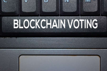 Blockchain Voting write on keyboard isolated on laptop background
