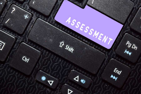 Assessment write on keyboard isolated on laptop background Stockfoto