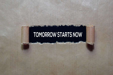 Tomorrow Starts Now Text written in torn paper Stockfoto