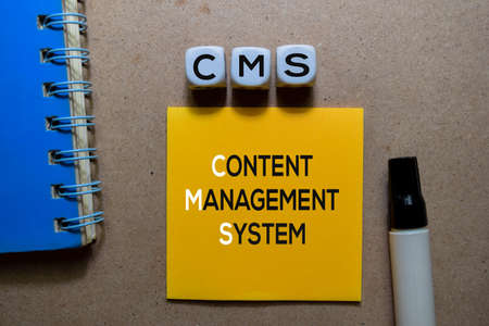 CMS - Content Management System write on Sticky note. Isolated on wooden table