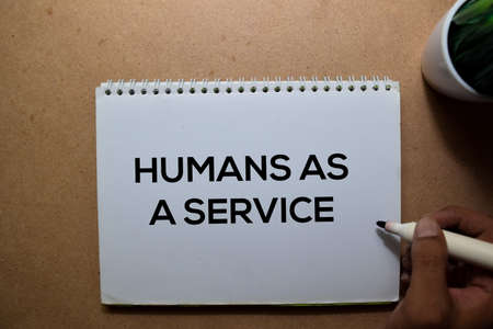 Humans As A Service write on a book. Isolated on Wooden Table Stockfoto